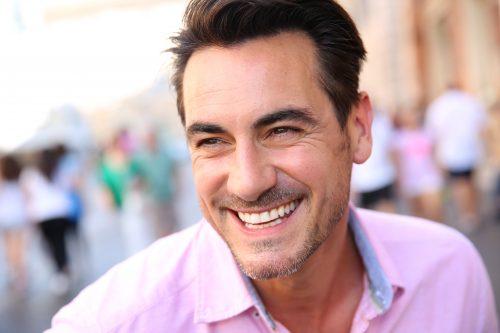 man in pink shirt smiling