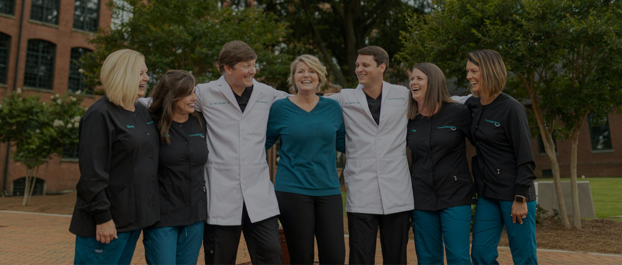 Current Dentistry Staff Standing Arm and Arm Together Laughing Outside
